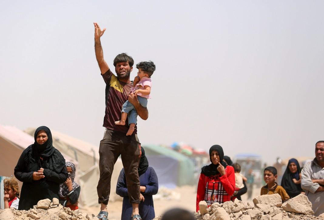 Un hombre con un niño en brazos levanta la mano (© AP Images)