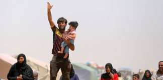 Man holding small child and waving ( © AP Images)