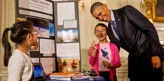 President Obama hugging girl next to her display (© AP Images)