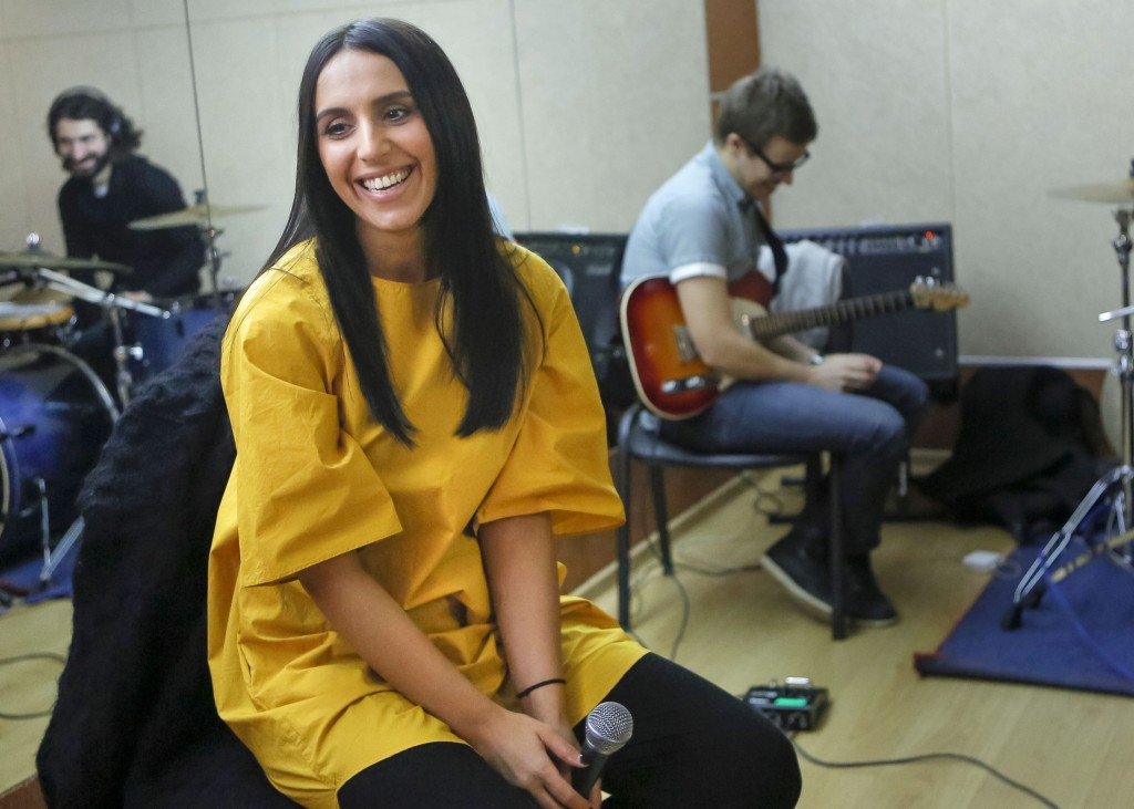 Jamala sitting and smiling in music studio as two other musicians sit in background (© AP Images)