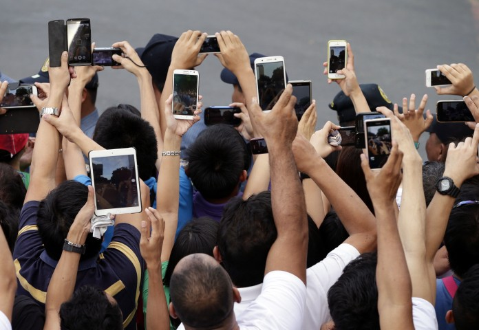 People holding up smartphones (© AP Images)
