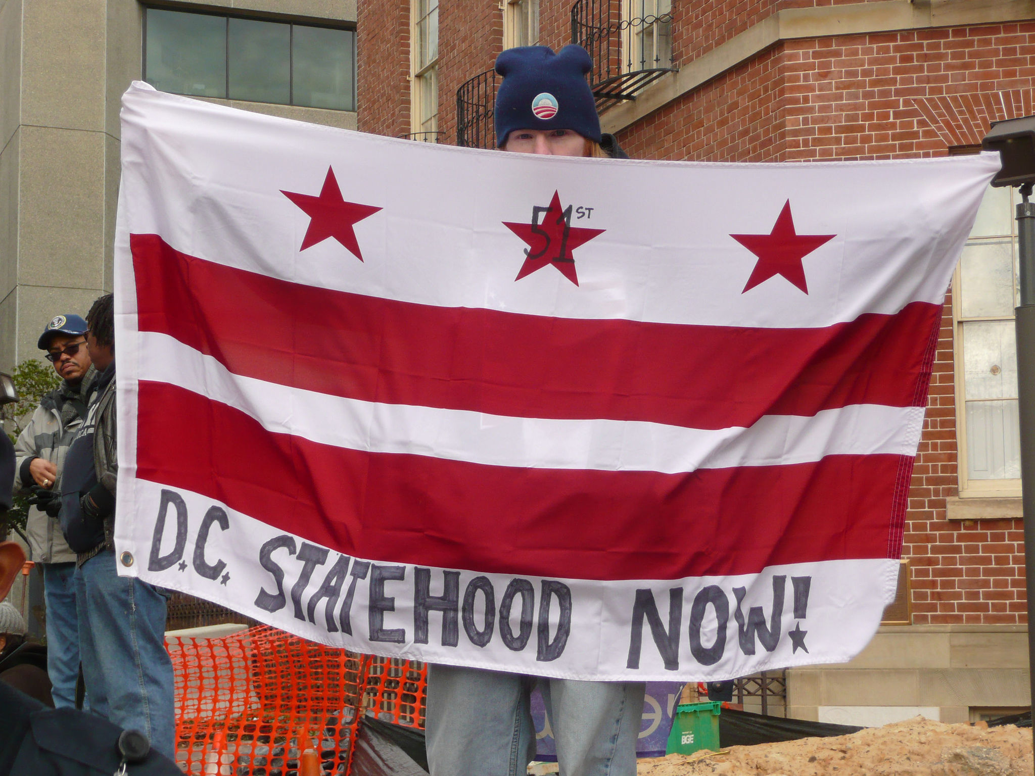 "Boy holding D.C. flag with ""D.C. statehood now!"" written on it (Djembayz/Creative Commons)"