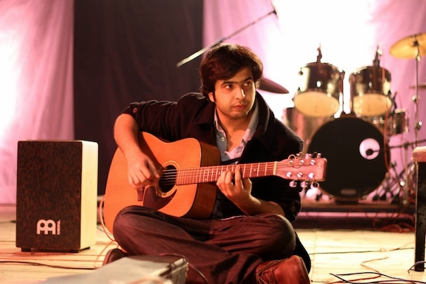 Man sitting cross-legged and playing guitar (Courtesy of Dosti Music Project)