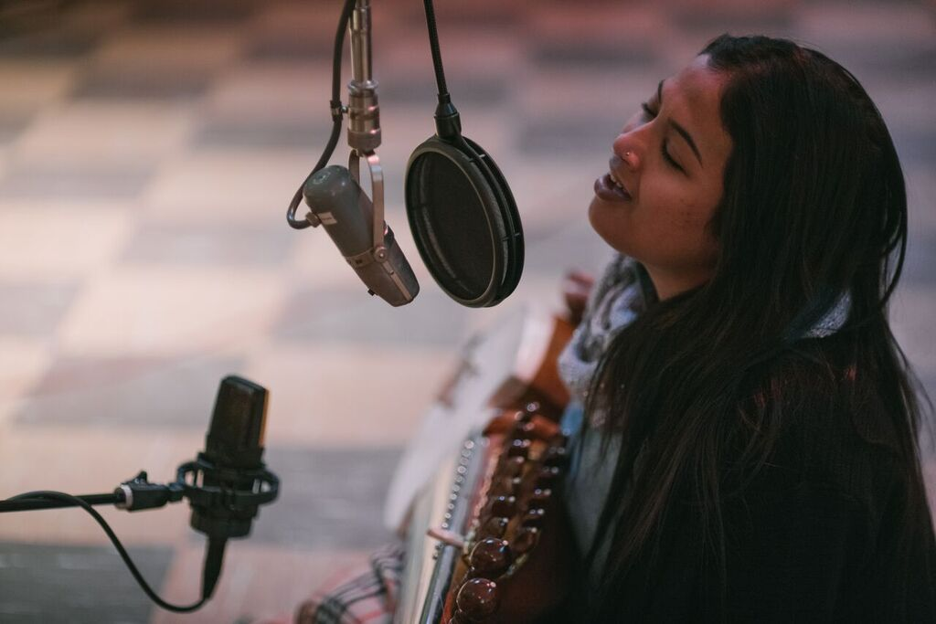 Woman singing into recording microphone and holding sarod (Courtesy of Dosti Music Project)
