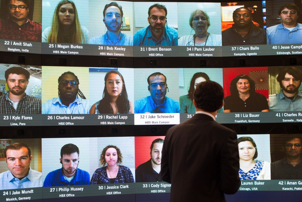 Person in front of screen displaying other people and names (© AP Images)