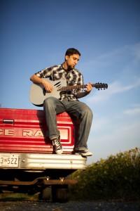 Raef Haggag playing guitar and sitting on back of pickup truck (Akbar Sayed)