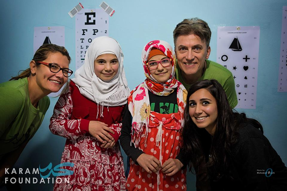 Two girls standing with medical professionals in front of eye charts (Courtesy of Karam Foundation)
