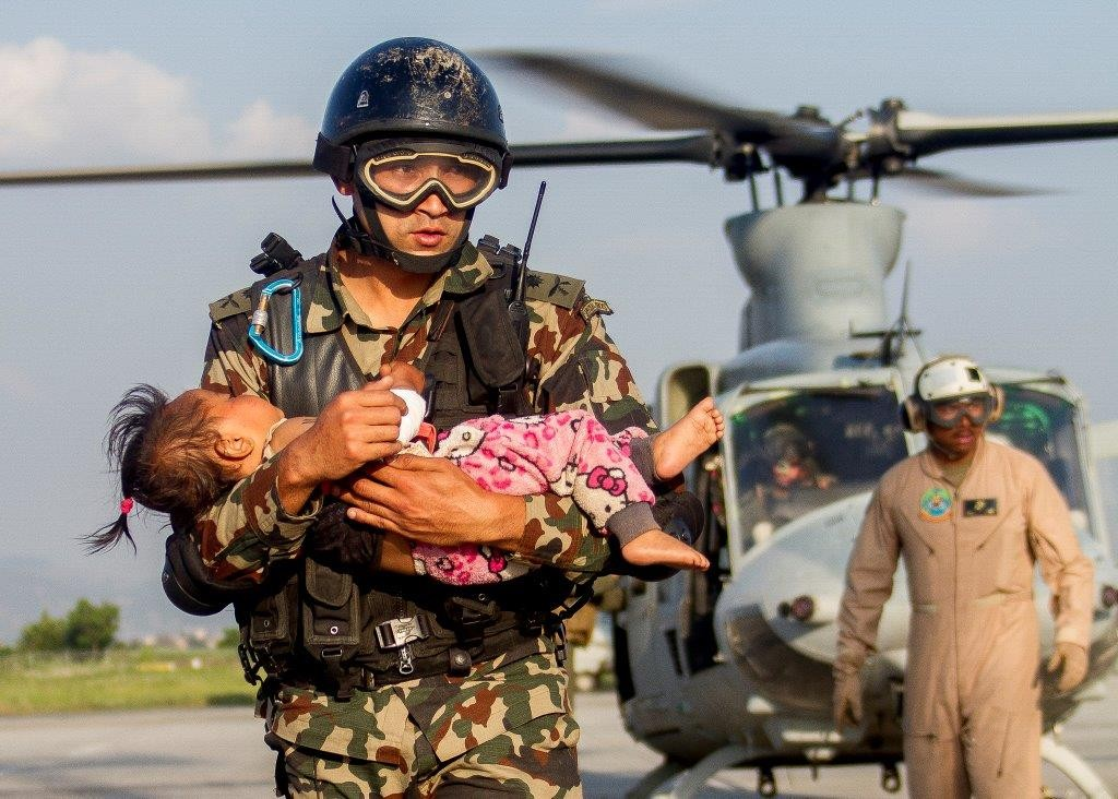 Soldier carrying young child in front of helicopter (DOD)