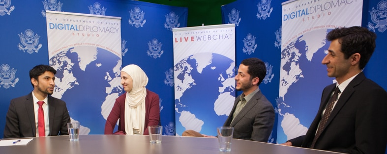 Woman with head covered by scarf conversing with three male panelists (State Dept./D.A. Peterson)