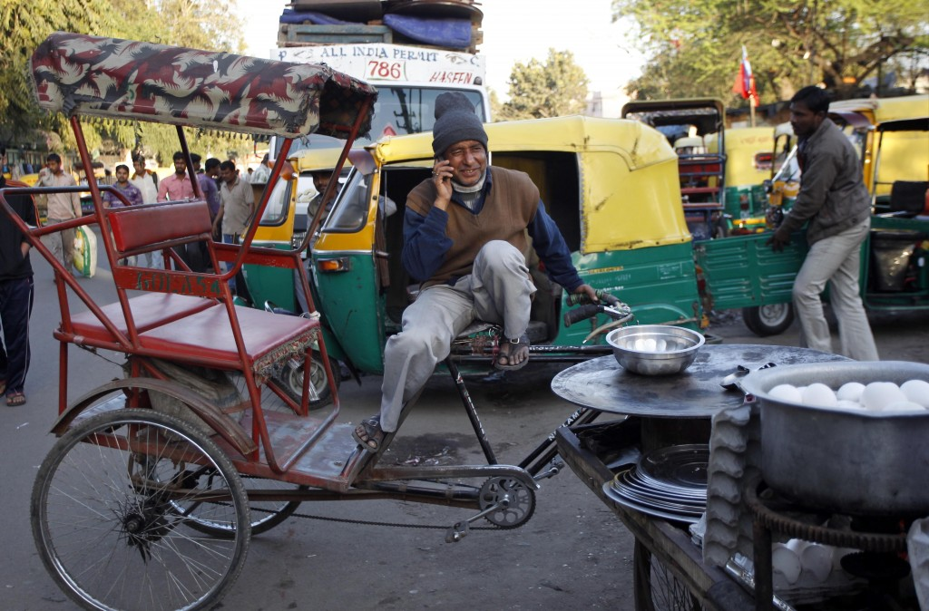 Person on mobile phone sitting on cycle rickshaw beside stove (© AP Images)