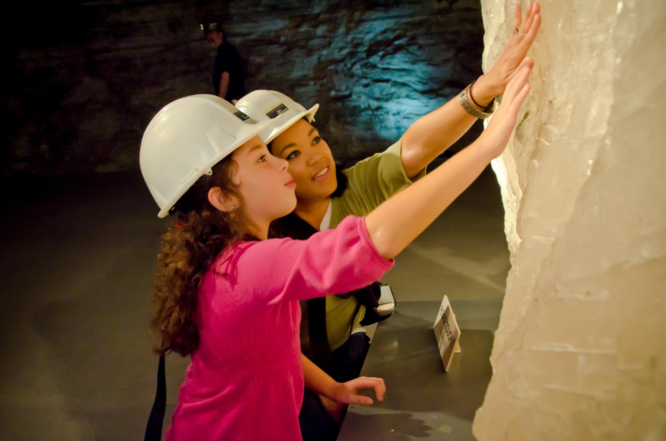دو زن در حال لمس کردن یک صخره نمکی بزرگ (استراتاکا)