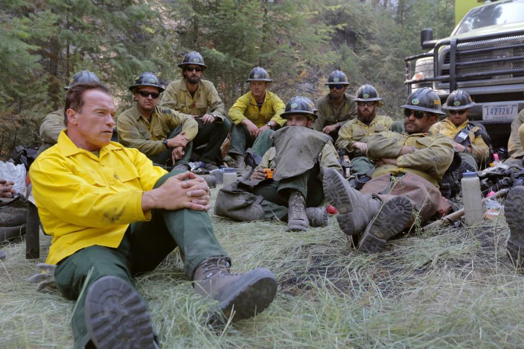 Arnold Schwarzenegger sentado en el bosque con bomberos (Foto cedida por «Years of Living Dangerously»)