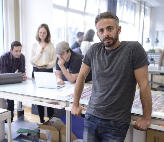 Man leaning on table with people talking in background (Shutterstock)