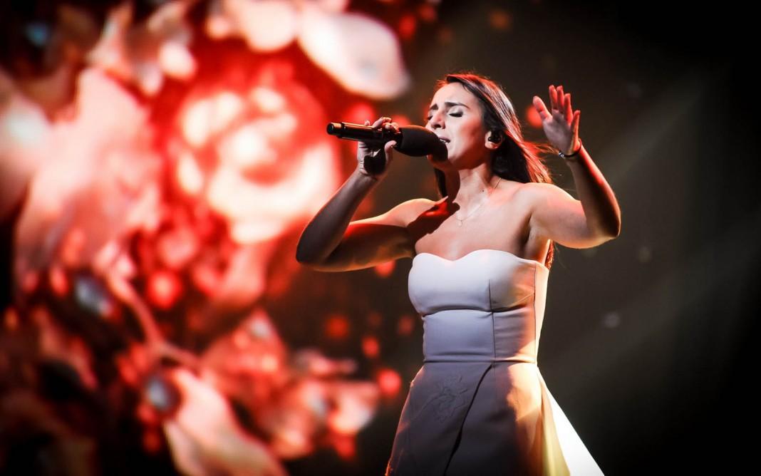 Jamala cantando en un escenario, con diseño floral de fondo (Shutterstock)