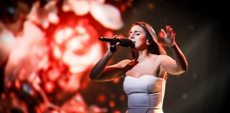 Jamala singing on stage, floral pattern in background (Shutterstock)