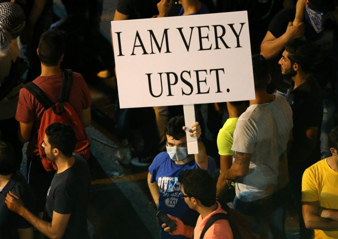 Crowd and man holding up sign that says 'I AM VERY UPSET' (© AP Images)