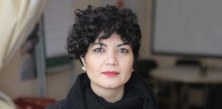 Tamila Tasheva in front of whiteboard and table (Courtesy of Tamila Tasheva)