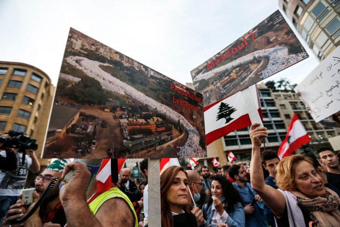 Protesters in Lebanon holding up signs (© AP Images)