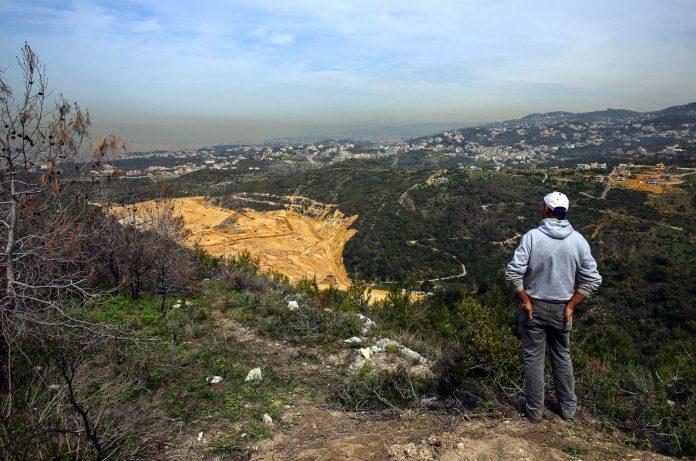 Man looking at landfill in Lebanon (© AP Images)