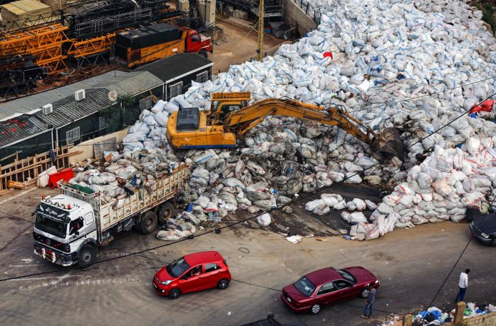 Work vehicles and street filled with bags of trash (© AP Images)