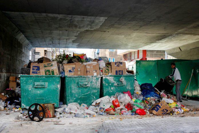 Man near overflowing trash bins in Lebanon (© AP Images)