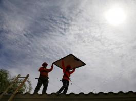افرادی در حال راه رفتن بر روی پشت بام هستند و یک نفر صفحه خورشیدی را حمل می کند (عکس از آسوشیتدپرس)