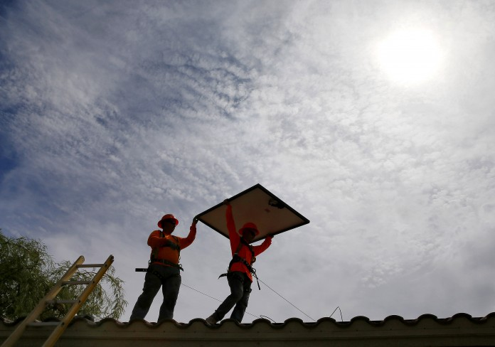 People walking on roof, one carrying solar panel (© AP Images)