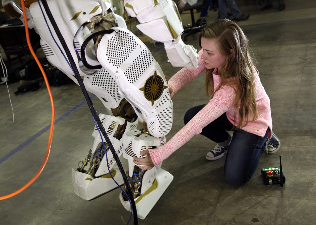 Une fille, à genoux, en train de manipuler la jambe d'un robot (© AP Images)