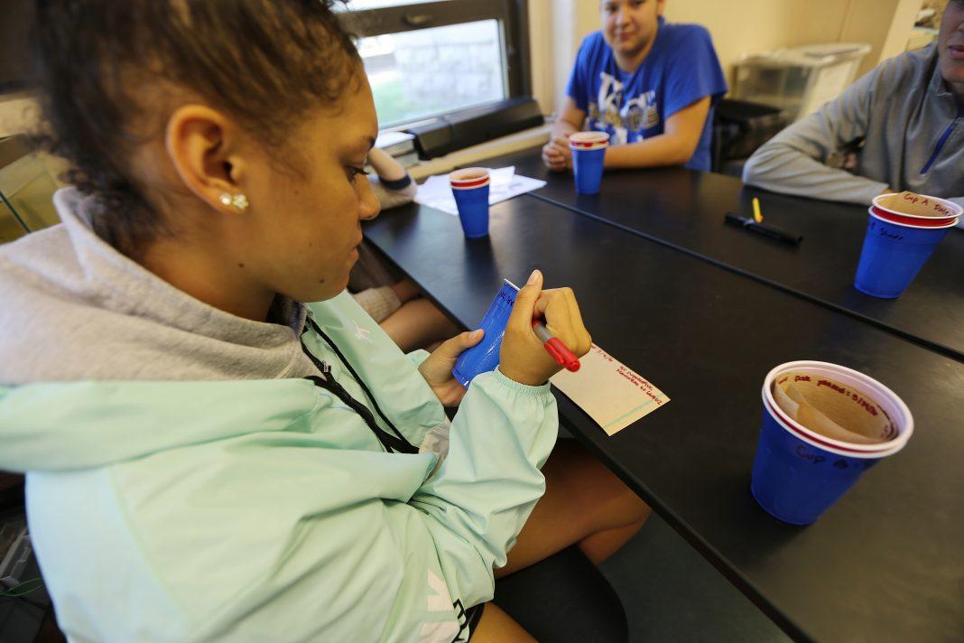 Estudiante escribe en un envase de plástico (© AP Images)