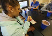 یک دانش آموز در حال نوشتن بر روی یک لیوان پلاستیکی (عکس از آسوشیتدپرس)
