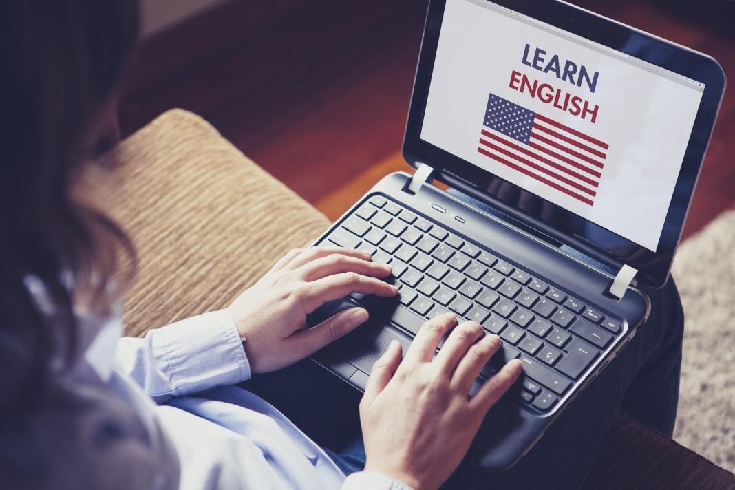 Студентка с ноутбуком изучает английский язык дома (© AP Images)