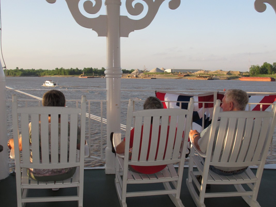 Passengers on Mississippi riverboat in rocking chairs (© AP Images)