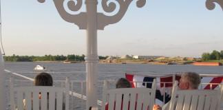 Des passagers sur le pont d'un bateau, assis dans des fauteuils à bascule (© AP Images)