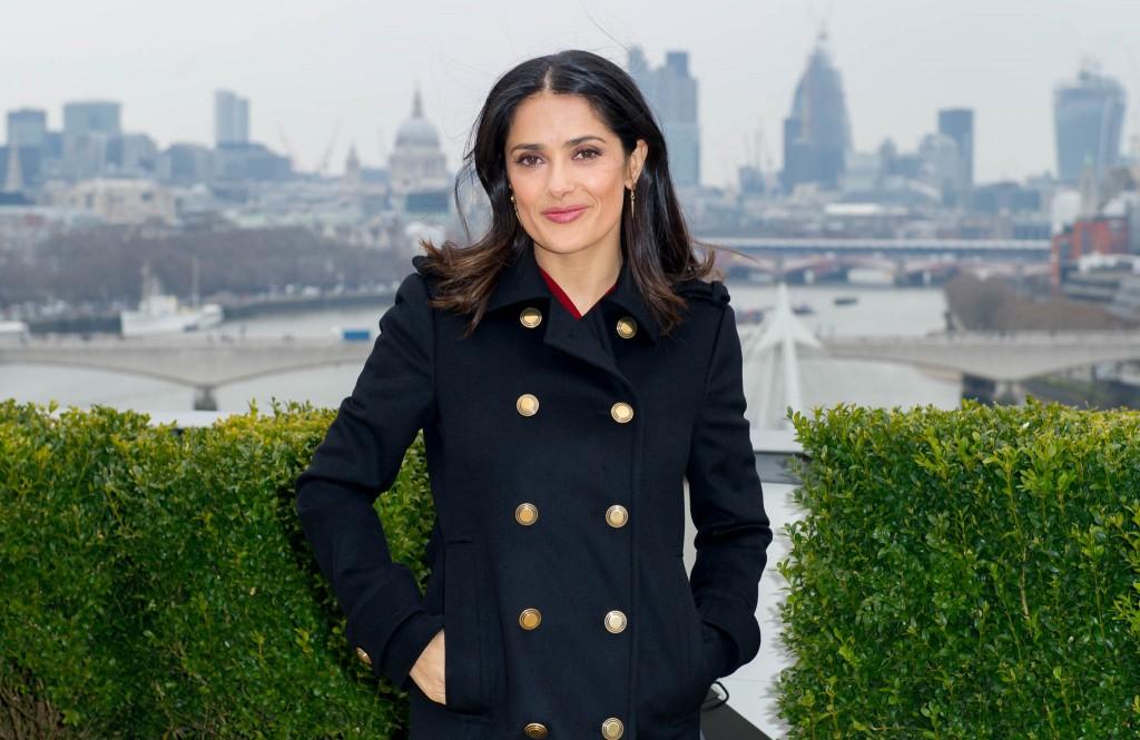 Salma Hayek posing in front of city skyline (© AP Images)