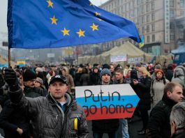Crowd of protesters holding signs and EU flag (© AP Images)