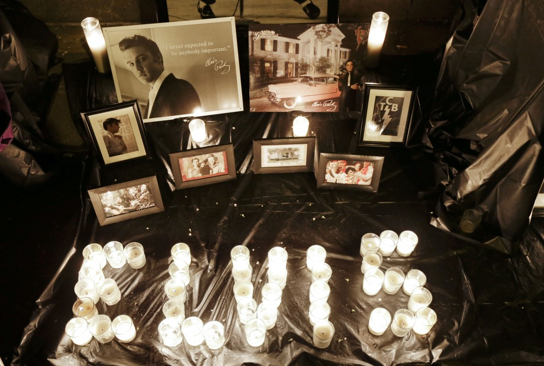 Arrangement of candles and framed photographs dedicated to musician Elvis Presley (© AP Images)