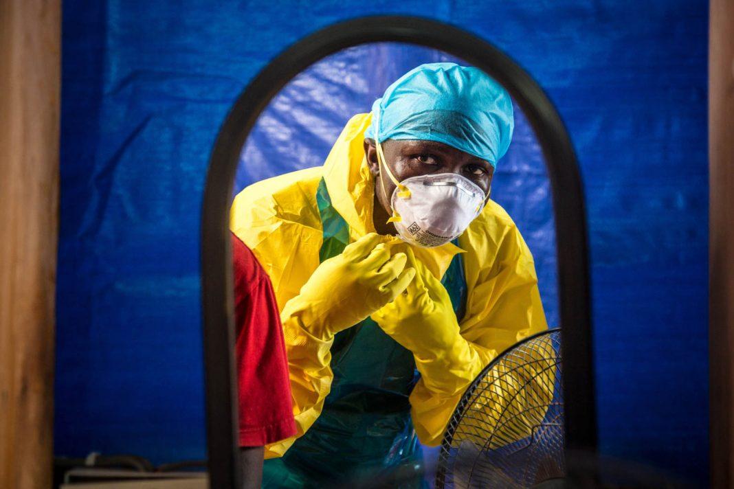 Reflejo de una persona que usa vestimenta de protección (© AP Images)