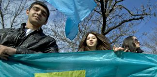 Young man and woman holding Crimean Tatar flag (© AP Images)