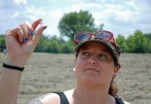 زنی یک قطعه الماس را میان انگشت شست و یک انگشت دیگر خود نگاه داشته است. (عکس پارک ایالتی گودال الماس/آسوشیتدپرس)