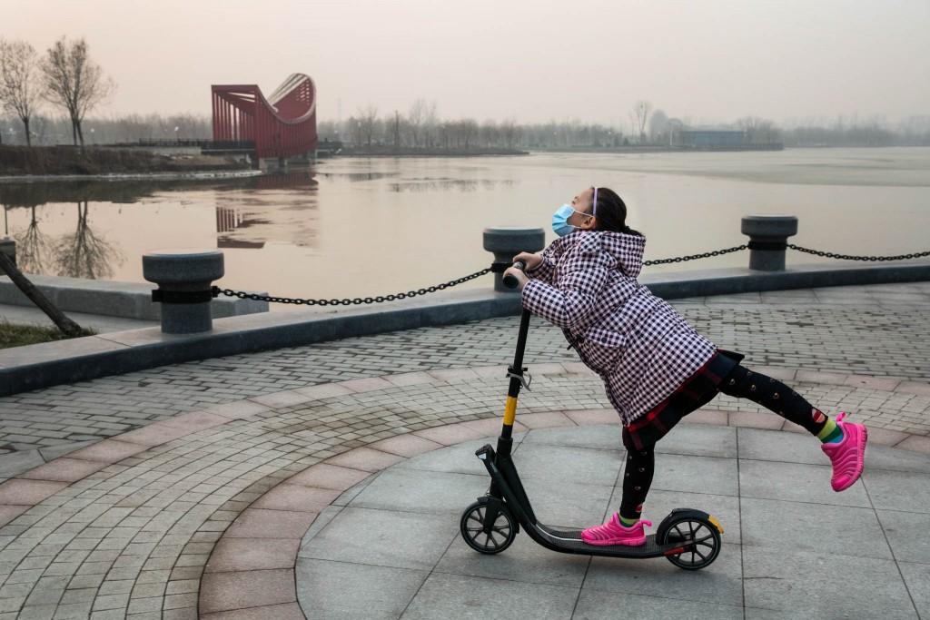 Gadis memakai masker mengendarai skuter (© AP Images)
