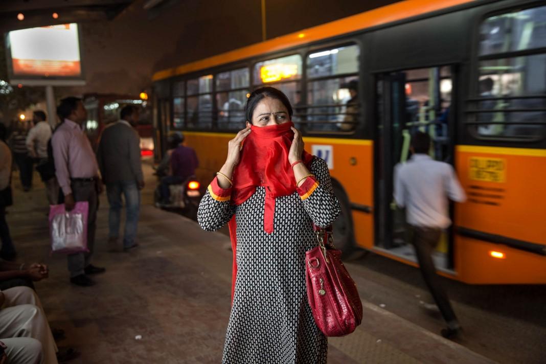 Mujer parada en estación de autobuses con la cara cubierta con un pañuelo (© AP Images)