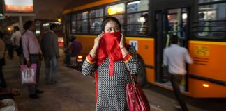 Woman standing at bus station covering her face with scarf (© AP Images)