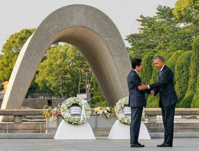 پرزیدنت اوباما و شینزو آبه، نخست وزیر ژاپن در حال دست دادن در برابر بنای یادمان صلح هیروشیما. ( عکس از آسوشیتدپرس)