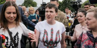 Nadiya Savchenko wearing a white T-shirt decorated with a trident — the symbol of Ukraine — talking to reporters as her sister, on left, looks on (© AP Images)