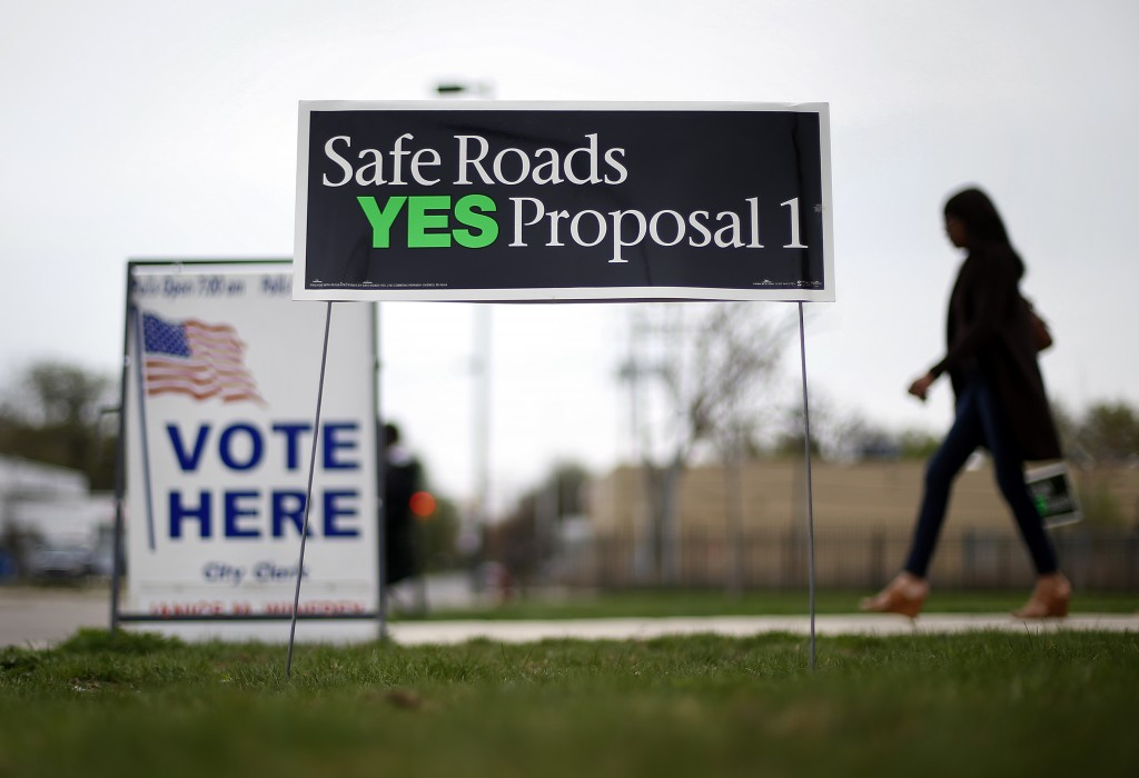 Election signs on lawn in foreground; woman walking by in background (© AP Images)