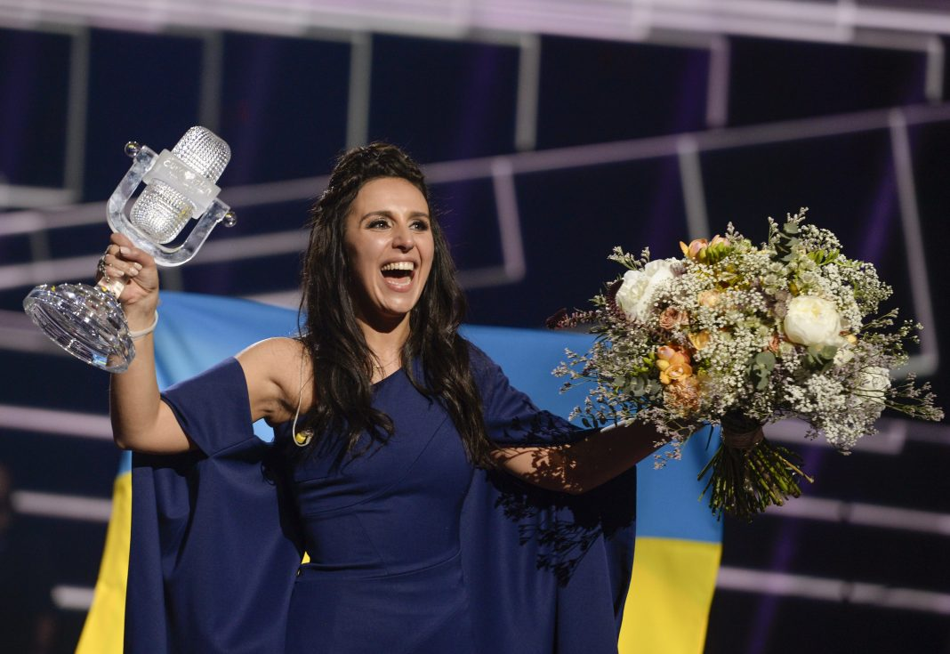 Jamala, wearing a dark blue evening dress, smiling and holding a trophy and a bouquet of flowers (© AP Images)