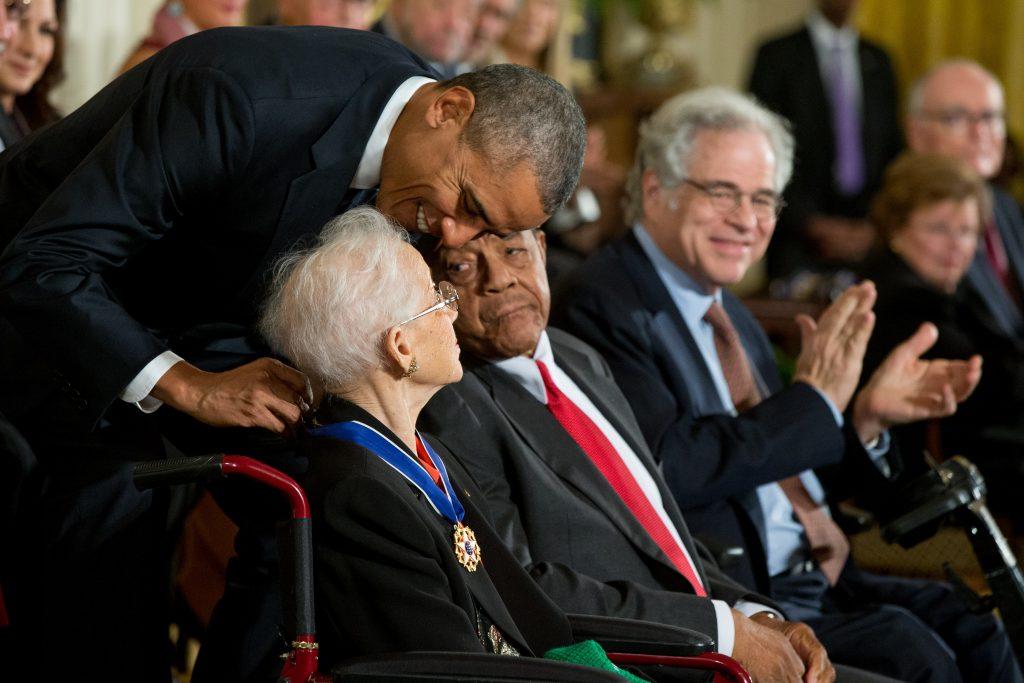 President Obama talking with seated Katherine Johnson (© AP Images)