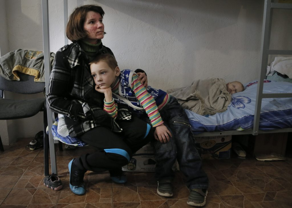 Woman and young boy sitting on bed while baby sleeps under blanket (© AP Images)