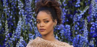 Rihanna standing in front of wall of flowers (© AP Images)
