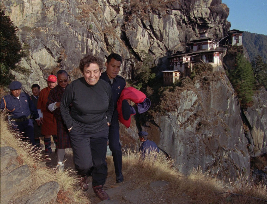 Donna Shalala climbing trail up mountain, people following behind (© AP Images)